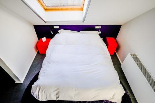Slaapkamer met rode nachtkastjes